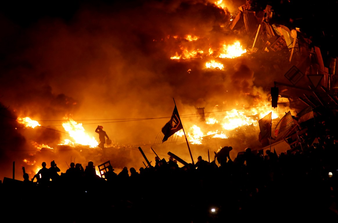 Anti-government protesters stand behind burning barricades in Kiev's Independence Square February 19, 2014. Ukrainian President Viktor Yanukovich accused pro-European opposition leaders on Wednesday of trying to seize power by force after at least 26 people died in the worst violence since the former Soviet republic gained independence. REUTERS/Vasily Fedosenko (UKRAINE - Tags: POLITICS CIVIL UNREST)